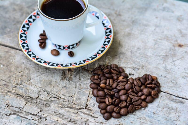 Taza de café y de habas en la forma de corazón fotos de archivo