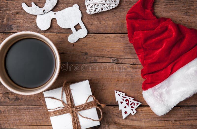 Taza de café y de sombrero de Santas, de sistema de la Navidad, de regalo y de árbol de navidad celebración imágenes de archivo libres de regalías