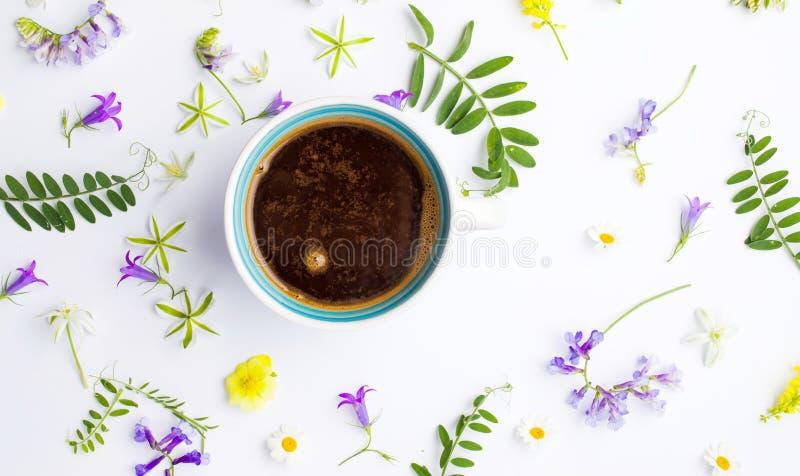 Taza de café y de flores coloridas en blanco fotografía de archivo libre de regalías