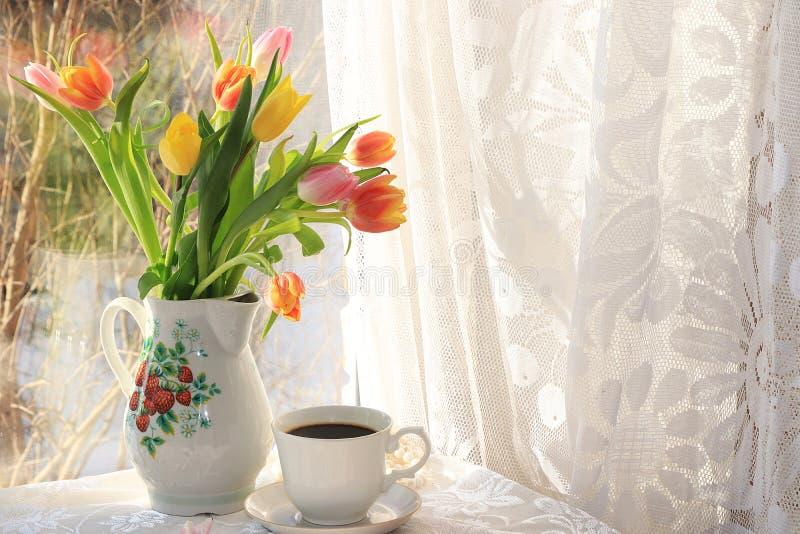 Taza de café y de flores en cinta festiva en fondo rosado foto de archivo