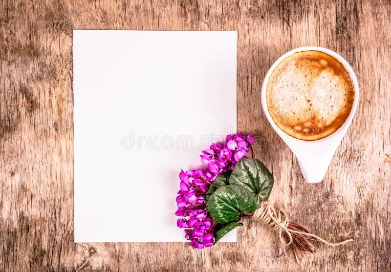 Taza de café y de flores Hoja de papel y taza de café vacías en la tabla fotografía de archivo