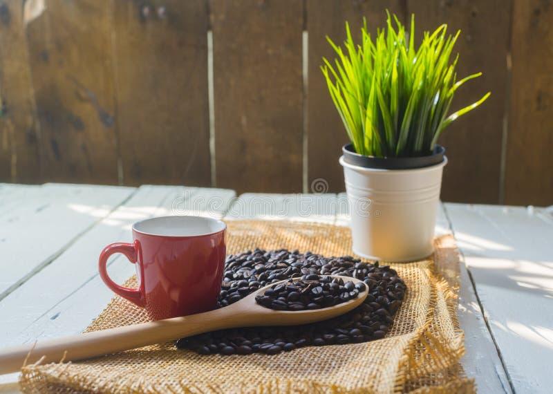 Taza de café y grano de café rojos con el saco en de madera blanco foto de archivo
