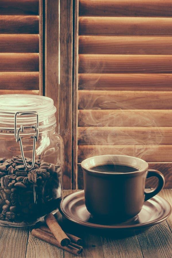 Taza de café y de granos de café calientes en el tarro de cristal contra ventana con los obturadores de madera imagen de archivo