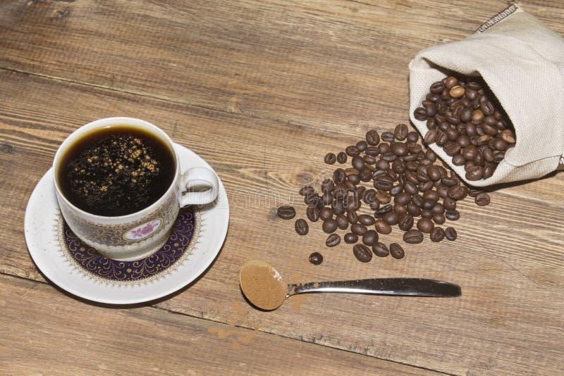 Taza de café y granos de café en bolso fotos de archivo