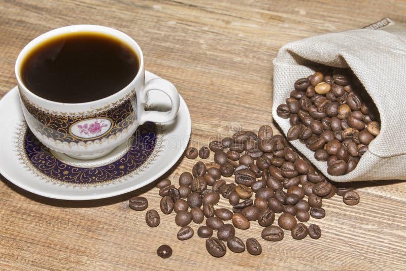 Taza de café y granos de café en bolso fotografía de archivo libre de regalías
