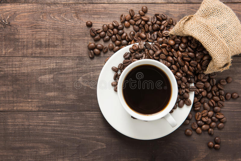 Taza de café y granos de café en fondo de madera Visión superior imagen de archivo libre de regalías