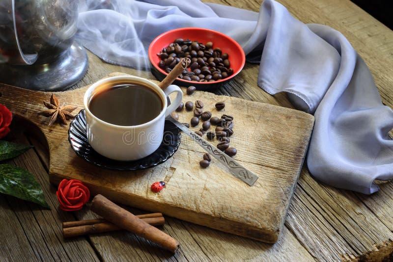 Taza de café y granos de café en la tabla de madera fotografía de archivo libre de regalías