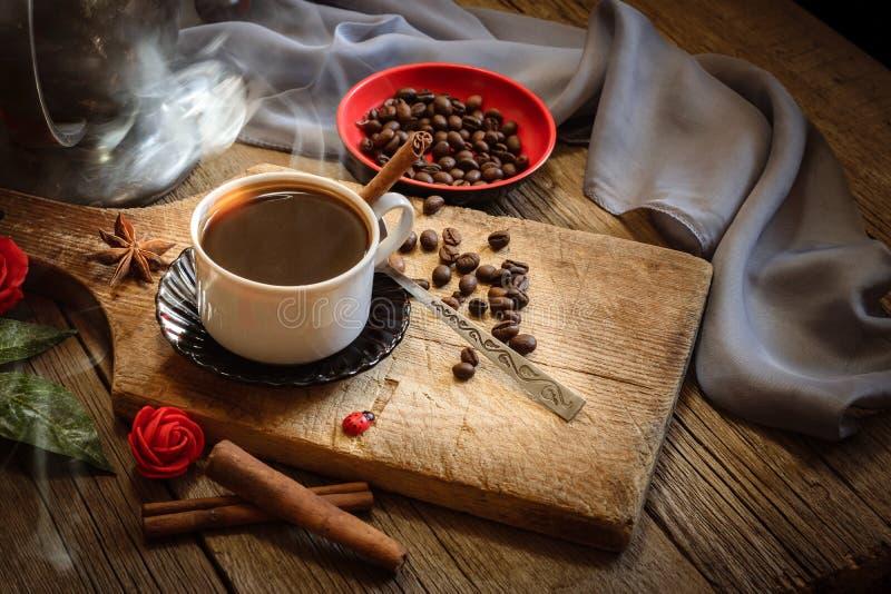 Taza de café y granos de café en la tabla de madera fotos de archivo libres de regalías