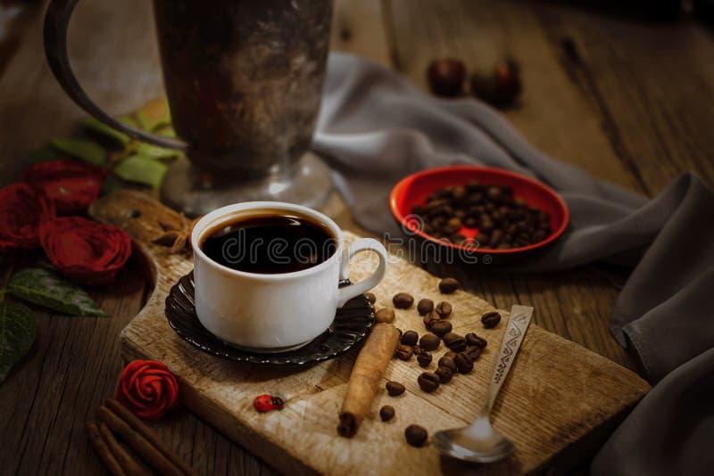 Taza de café y granos de café en la tabla de madera fotografía de archivo