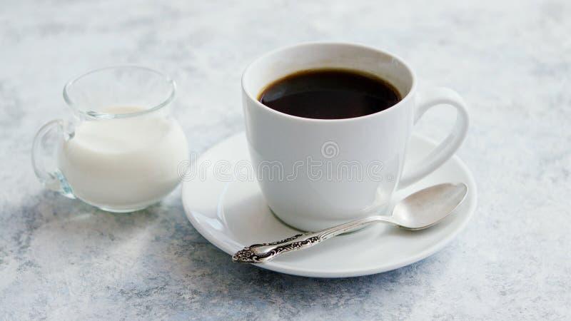 Taza de café y de jarra de leche imagenes de archivo