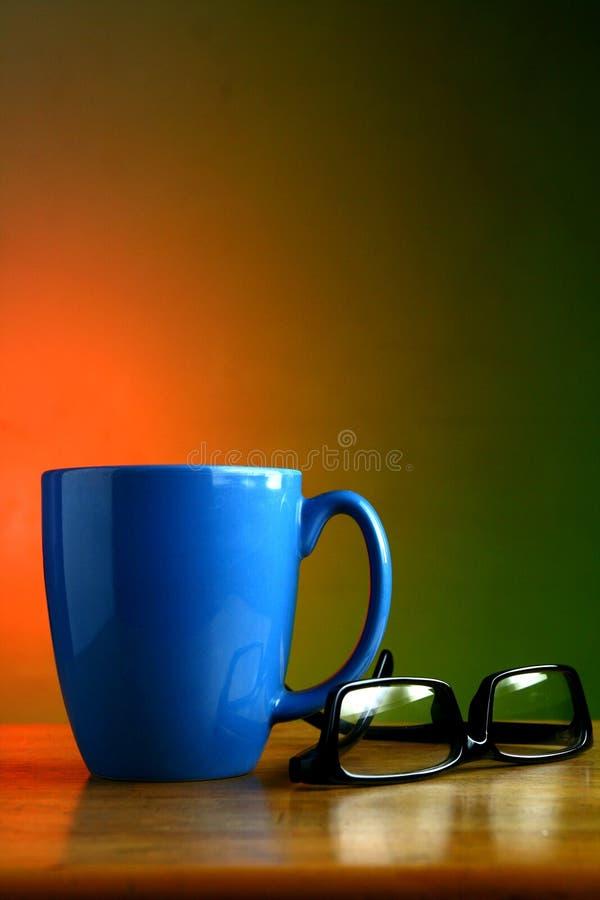 Taza de café y lentes azules imágenes de archivo libres de regalías