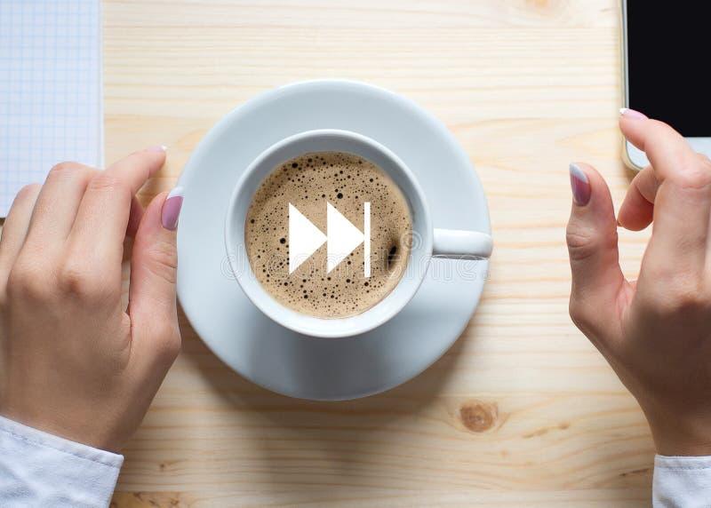 Taza de café y de manos femeninas en las mangas blancas en el fondo de madera, visión superior, cierre para arriba Acelere el ico imagenes de archivo