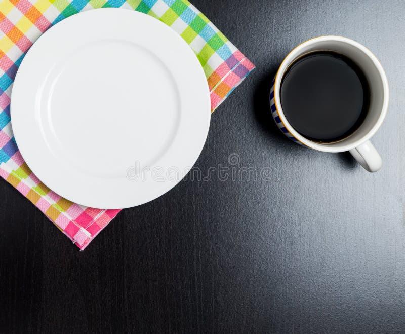 Taza de café y placa en blanco para el bocado en la tabla negra brillante fotos de archivo libres de regalías