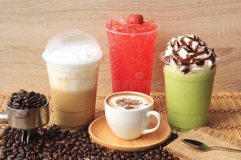 Taza de caf? caliente con los granos de caf? en la tabla de madera, el caf? fr?o, el t? verde helado del matcha y la soda de la f foto de archivo libre de regalías