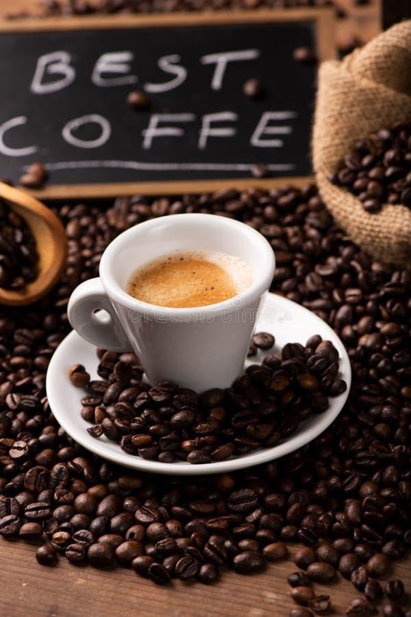 Taza de caf? rodeada por los granos de caf? fotografía de archivo