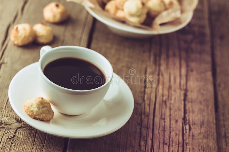 Taza de caf? y de galletas hechas en casa del coco en el postre sabroso del coco del viejo del fondo espacio horizontal de madera fotos de archivo libres de regalías