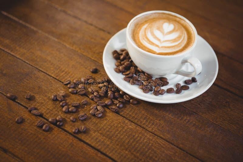 Taza de capuchino con arte del café y granos de café imagen de archivo libre de regalías
