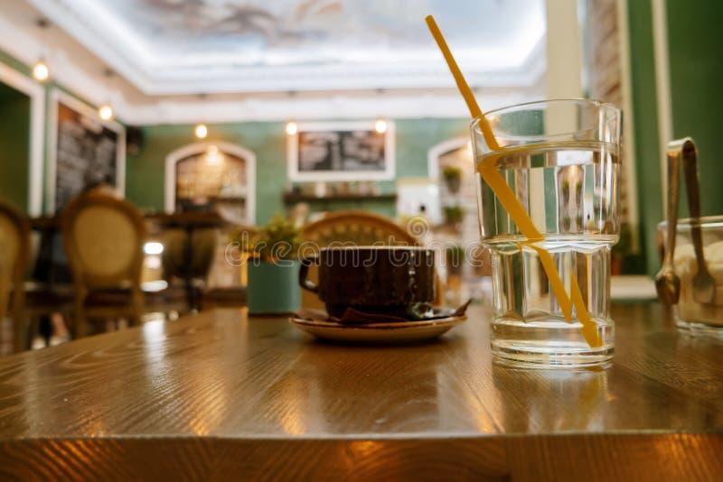 Taza de capuchino y vidrio de agua en la tabla, fondo de la cafetería, tono caliente fotografía de archivo