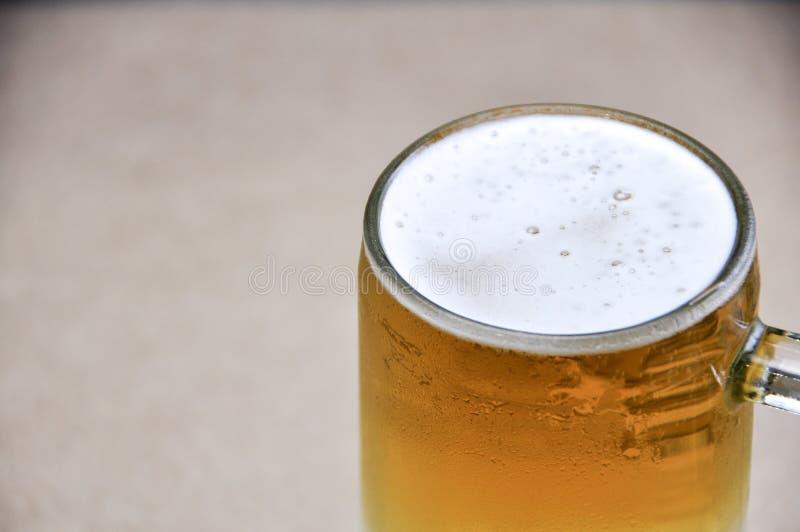 Taza de cerveza en el fondo blanco imagen de archivo