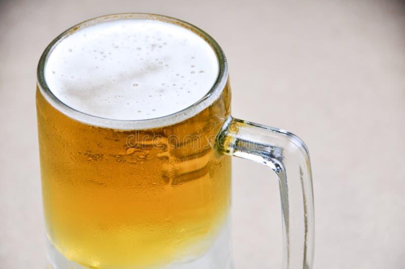 Taza de cerveza en el fondo blanco imágenes de archivo libres de regalías