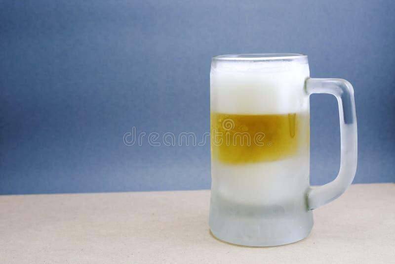Taza de cerveza en el fondo blanco foto de archivo
