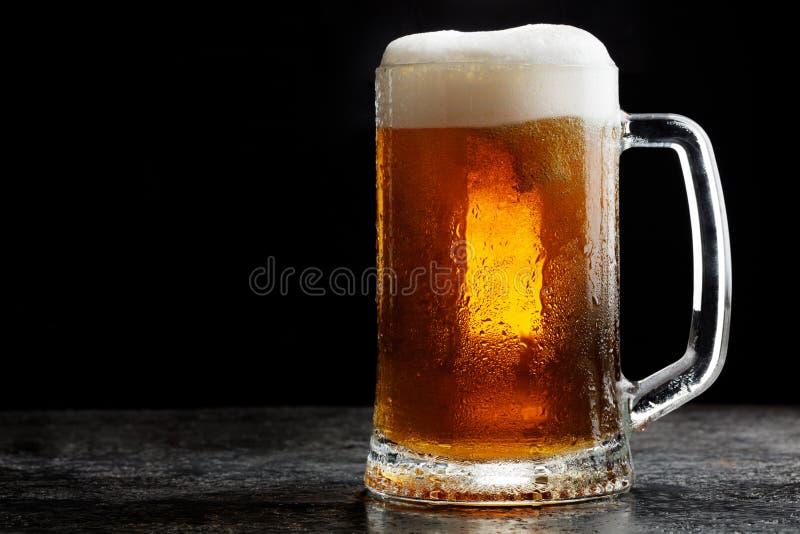 Taza de cerveza ligera del arte frío en fondo oscuro foto de archivo