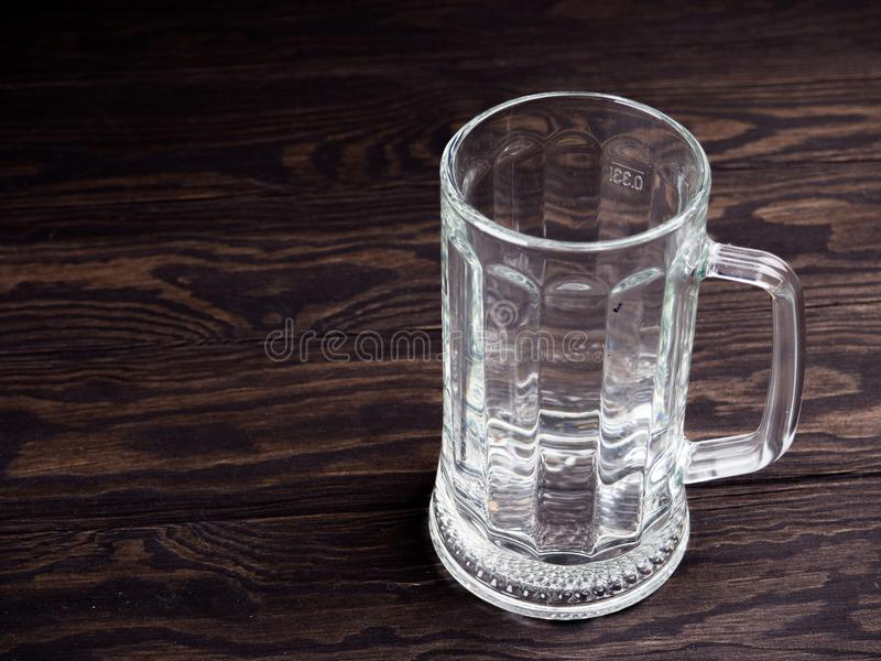 Taza de cerveza vacía, pinta vacía grande de cerveza en la tabla de madera vieja imágenes de archivo libres de regalías