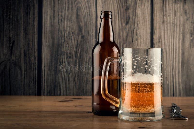 Taza de cerveza y botella de cerveza fotografía de archivo libre de regalías