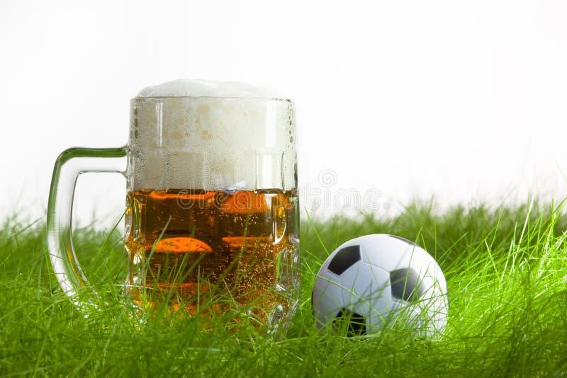 Taza de cerveza y de balón de fútbol en hierba fotos de archivo