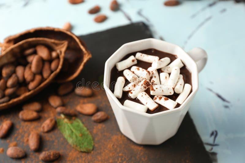 Taza de chocolate caliente con las melcochas en la placa de la pizarra fotos de archivo