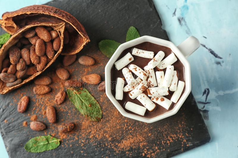 Taza de chocolate caliente con las melcochas en la placa de la pizarra foto de archivo