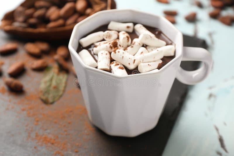 Taza de chocolate caliente con las melcochas en la placa de la pizarra imagenes de archivo