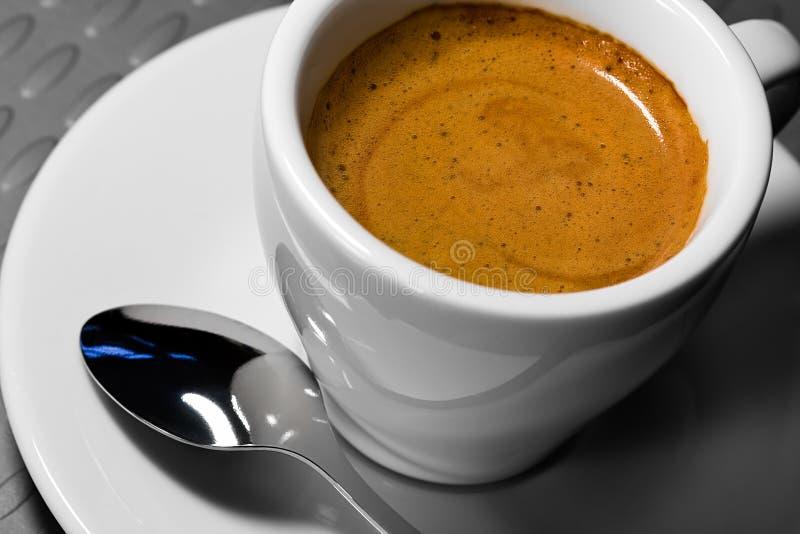 Taza de cofee en un platillo con una cuchara foto de archivo