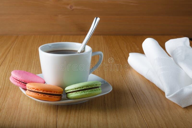 Taza de Coffe con el macaron francés colorido imagenes de archivo