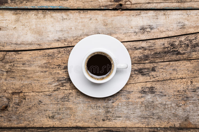 Taza de coffe negro fuerte en la tabla de madera foto de archivo