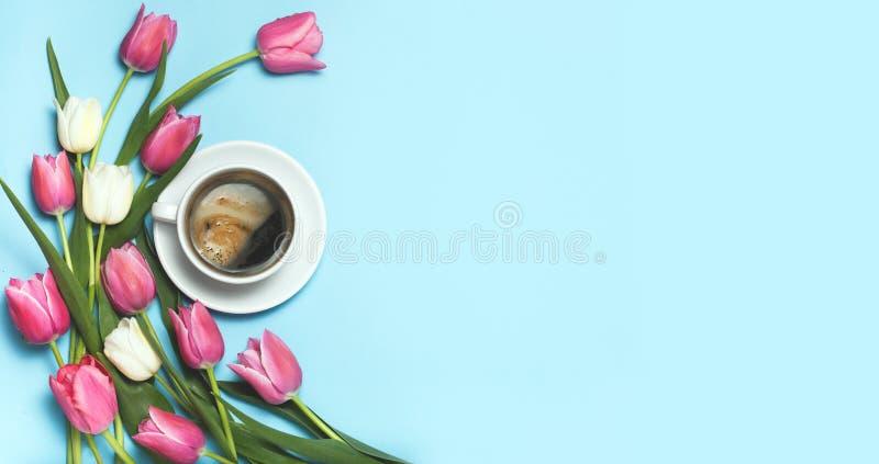 Taza de coffe y tulipanes rosados en fondo azul imagenes de archivo