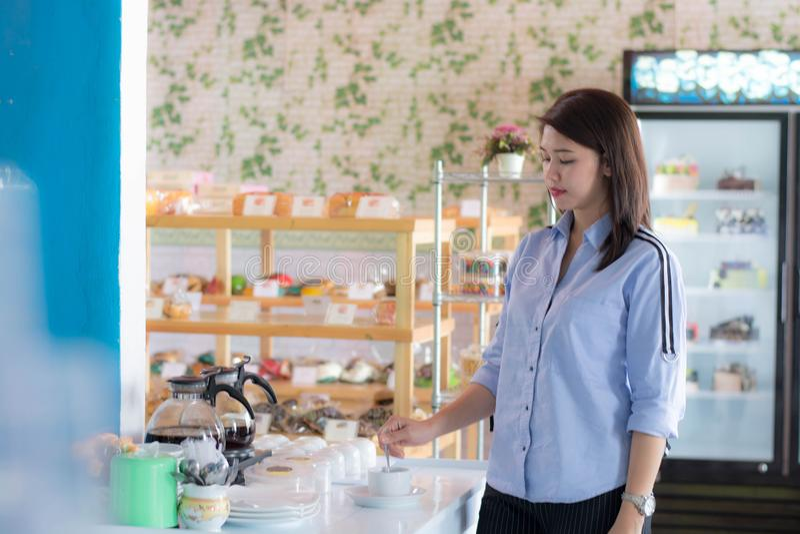Taza de colada femenina asi?tica de Attracive de caf? de la caldera del fabricante de caf? en la torta imagenes de archivo
