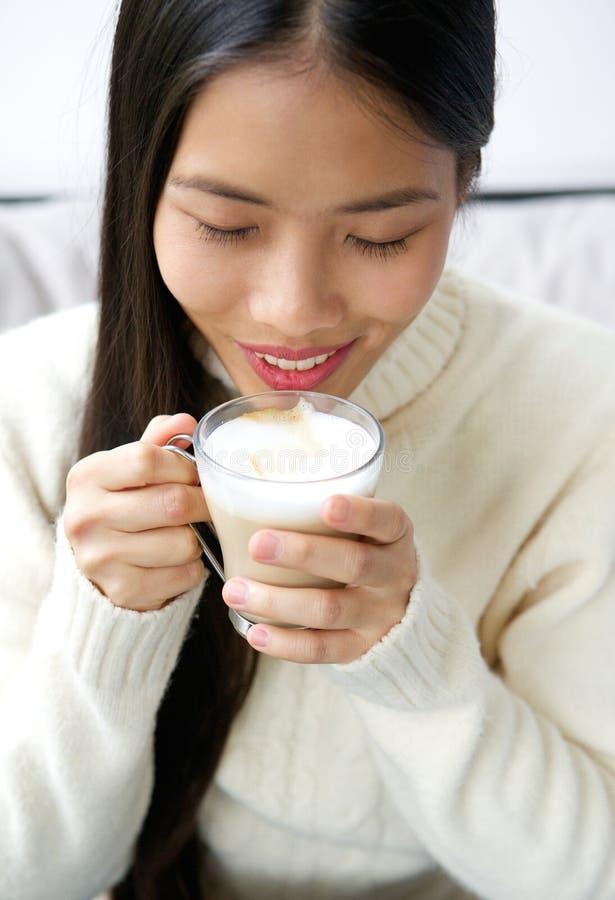 Taza de consumición asiática joven atractiva de la mujer de café imagen de archivo