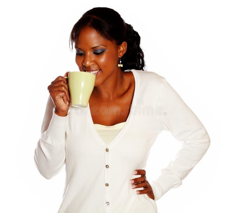 Taza de consumición femenina joven sonriente atractiva del té foto de archivo libre de regalías