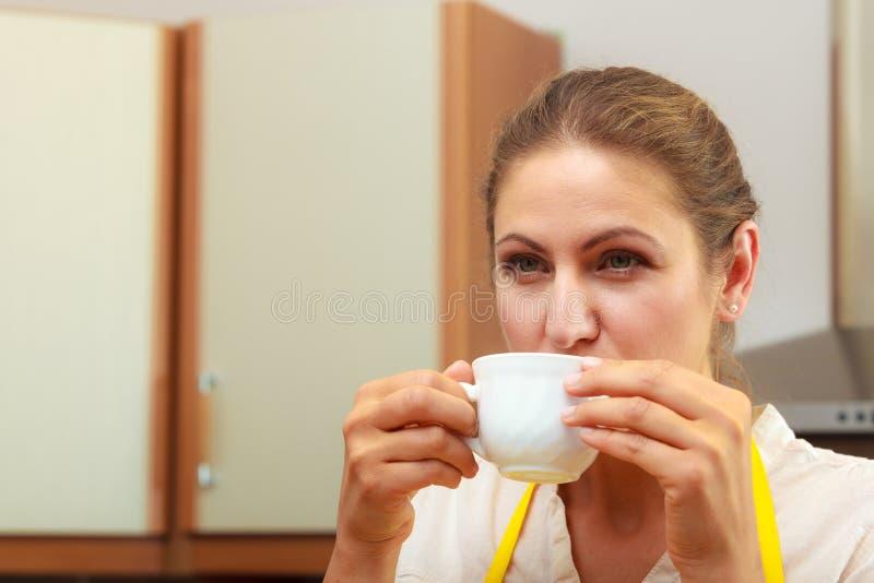 Taza de consumición madura de la mujer de café en cocina fotos de archivo
