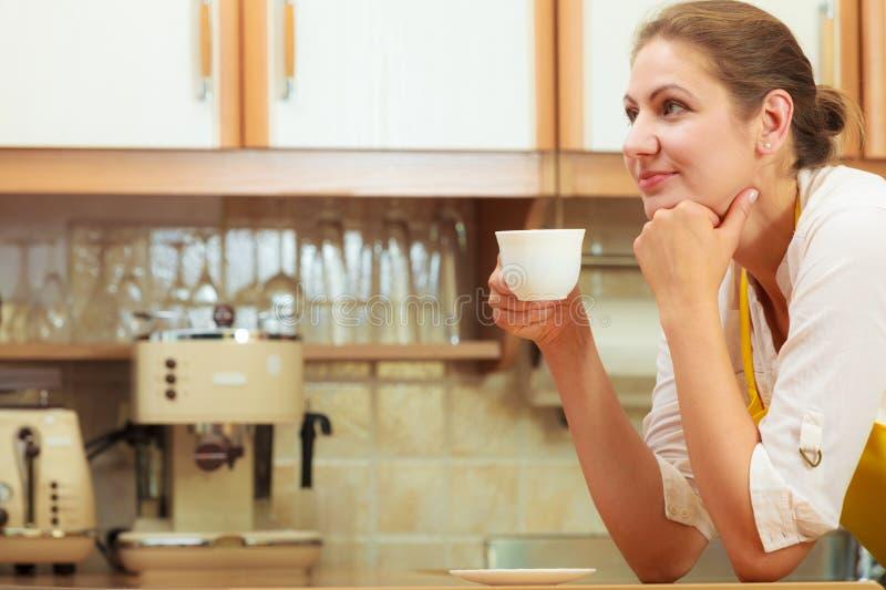 Taza de consumición madura de la mujer de café en cocina fotografía de archivo