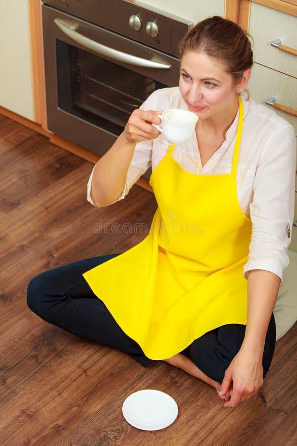 Taza de consumición madura de la mujer de café en cocina imágenes de archivo libres de regalías