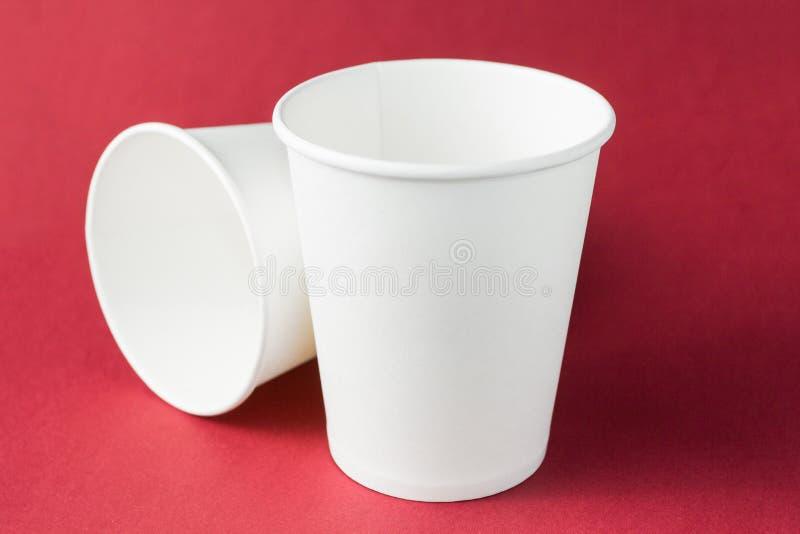 Taza de consumición para llevar de papel del café con leche para el té, el café caliente y el jugo aislados en el fondo rojo, maq imagen de archivo libre de regalías