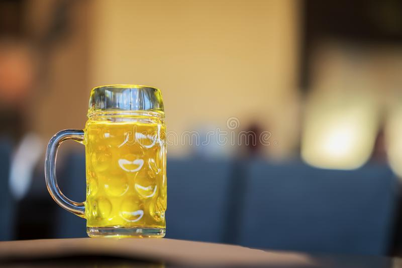 Taza de cristal de cerveza ligera de oro en barra, en cierre del pub para arriba Escena real Cultura de la cerveza, cervecería de fotos de archivo libres de regalías