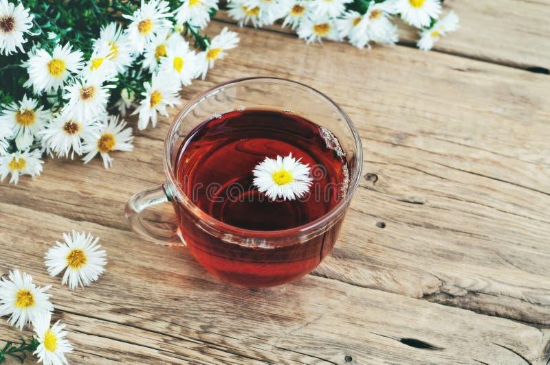Taza de cristal de té con un ramo de margaritas fotografía de archivo libre de regalías