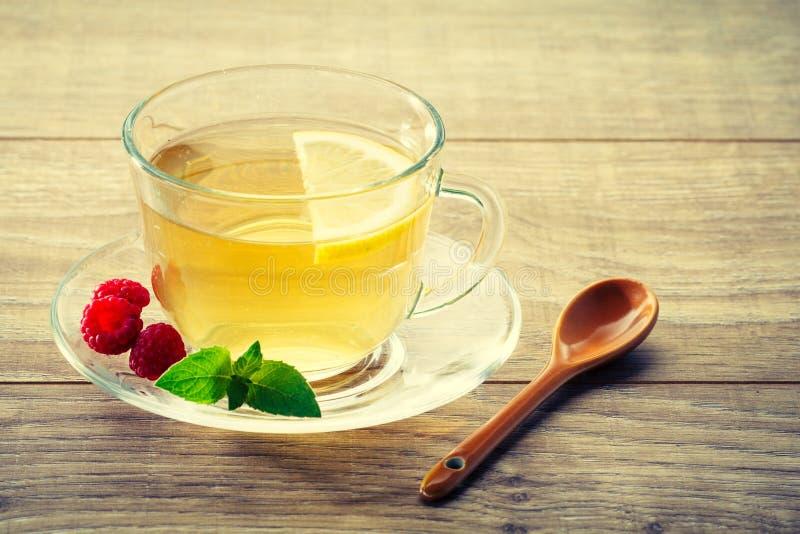 Taza de cristal de té verde con la rebanada del limón, hojas de la menta, fres imagen de archivo