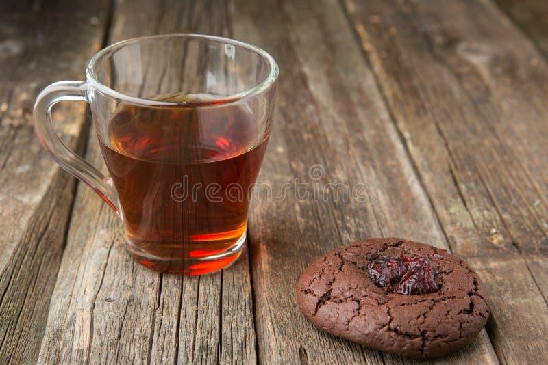 Taza de cristal de galleta caliente del té negro y del chocolate imágenes de archivo libres de regalías