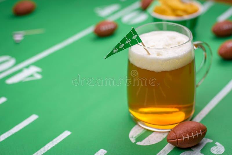 Taza de cristal grande de cerveza fría en la tabla con la decoración del partido del superbowl fotos de archivo