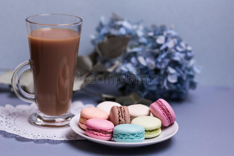 Taza de cristal de la mañana del primer de café con leche, macaron de la torta y la flor en la tabla azul Postre hermoso imagen de archivo libre de regalías