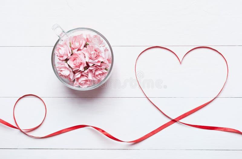 Taza de cristal llena de rosas rosadas con la cinta en forma de corazón roja en whi imágenes de archivo libres de regalías